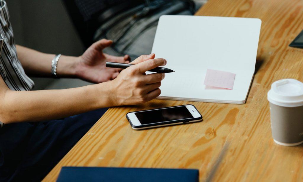 на столе блокнот для записей и телефон для планирования нового контента по рекомендациям по созданию эффективного контента