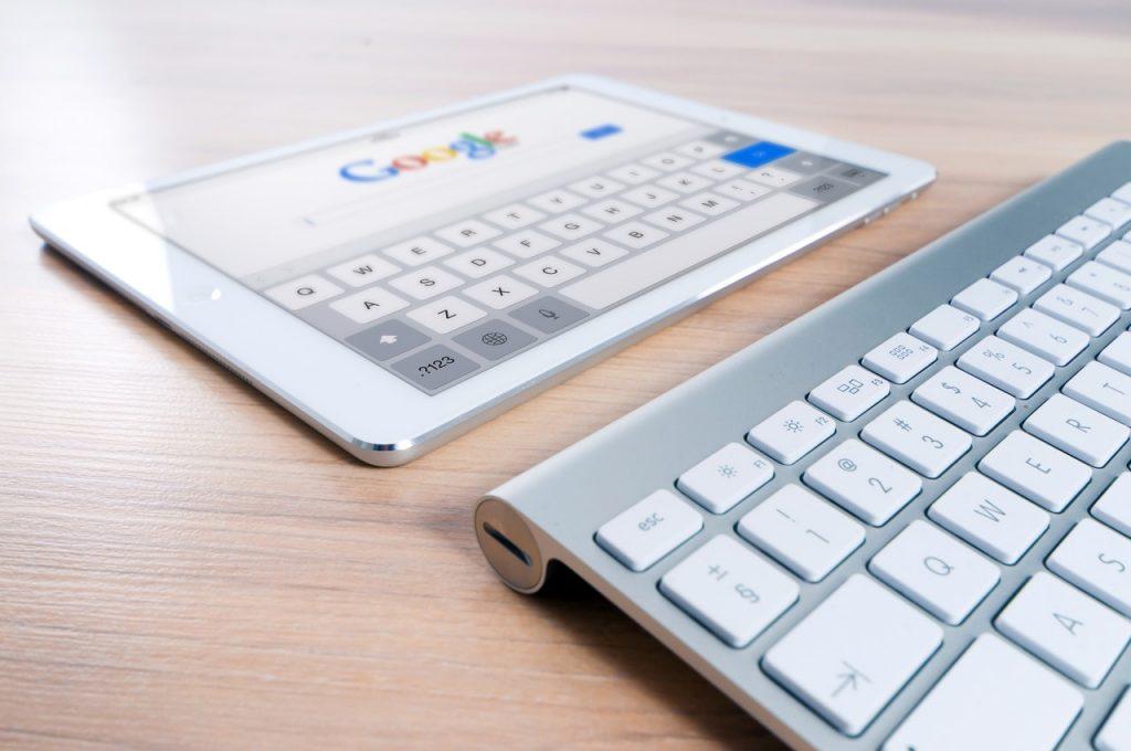 Планшет на столе с открытой стартовой страницей Google символизирует тему в статье, как ускорить индксацию страниц