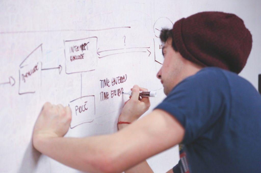 Молодой человек составляет техническое задание для статей в миралинкс на доске